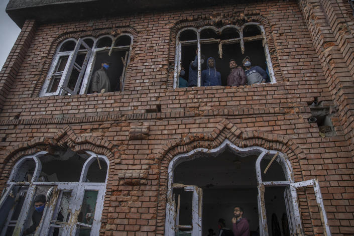 Kashmiri villagers inspect a mosque partially damaged during a gunbattle in Shopian, south of Srinagar, Indian controlled Kashmir, Friday, April 9, 2021. Seven suspected militants were killed and four soldiers wounded in two separate gunfights in Indian-controlled Kashmir, officials said Friday, triggering anti-India protests and clashes in the disputed region. (AP Photo/ Dar Yasin)