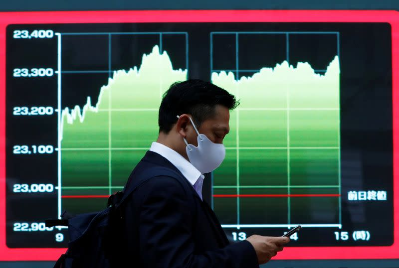 FILE PHOTO: A man wearing a protective face mask walks past a screen displaying a graph showing recent Nikkei share average outside a brokerage, amid the coronavirus disease (COVID-19) outbreak, in Tokyo