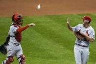St. Louis Cardinals catcher Yadier Molina throws Adam Wainwright a rosin bag after the first game of a baseball doubleheader against the Milwaukee Brewers Wednesday, Sept. 16, 2020, in Milwaukee. Wainwright pitched a complete game as the Cardinals won 4-2. (AP Photo/Morry Gash)