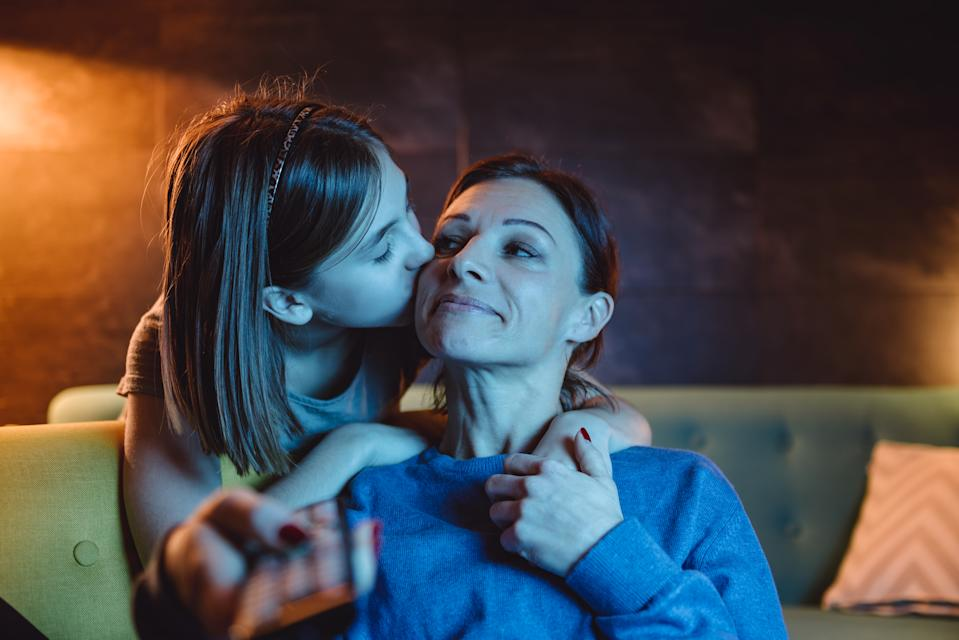 Mother sitting on sofa and watching TV late at night while daughter giving her goodnight kiss