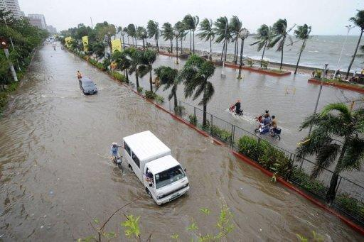 Commuters drive in flood waters brought on by Typhoon Saola on a road in Manila. More than 150,000 people across the Philippines have been forced to flee their homes this week as Typhoon Saolo, hovering to the north of the country, has added to monsoon weather, the national disaster management council said