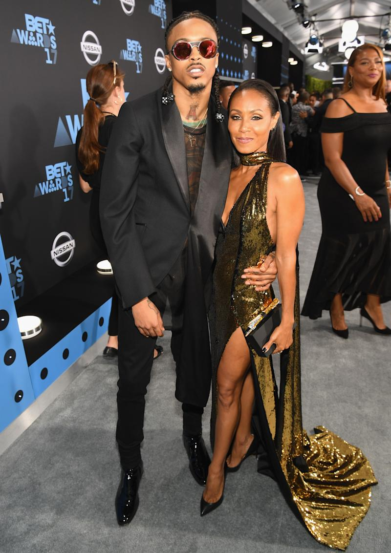 August Alsina and Jada Pinkett sport black and gold color outfitt at an event, and they look dazzling