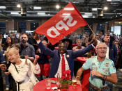 SPD supporters and members cheer at the election party of the Berlin SPD after the first forecasts for the outcome of the elections to the House of Representatives were announced, in Berlin, Sunday, Sept. 26, 2021. Exit polls show the center-left Social Democrats in a very close race with outgoing Chancellor Angela Merkel's bloc in Germany's parliamentary election, which will determine who succeeds the longtime leader after 16 years in power. (Bernd Von Jutrczenka/dpa via AP)