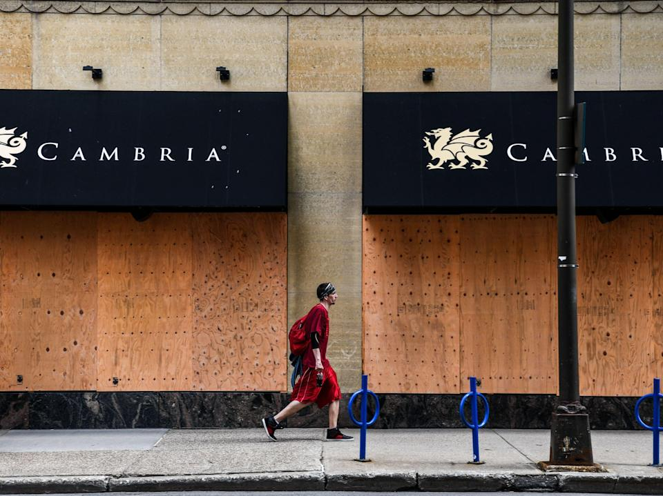 A man walks past a boarded business center near the Hennepin County Government Center in Minneapolis, Minnesota on 18 April, 2021AFP via Getty Images