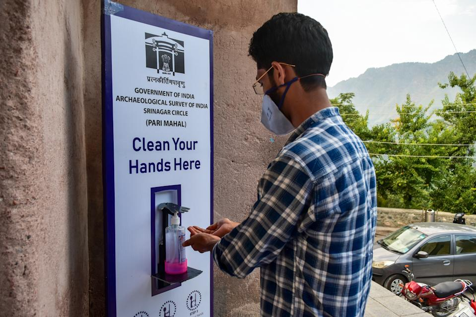 KASHMIR, JAMMU & KASHMIR, INDIA - 2020/07/09: A visitor seen sanitising his hands outside the Pari Mahal (The Palace of Fairies ) garden. The government in Kashmir valley has re-opened the parks and gardens to the public after being shut for more than four months due to the coronavirus pandemic. The deadly COVID-19 outbreak, has claimed over 148 lives and infected nearly 9,000 people so far. (Photo by Saqib Majeed/SOPA Images/LightRocket via Getty Images)