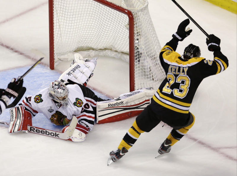 Boston Bruins center Chris Kelly (23) celebrates his goal past Chicago Blackhawks goalie Corey Crawford (50)during the first period in Game 6 of the NHL hockey Stanley Cup Finals, Monday, June 24, 2013, in Boston. (AP Photo/Charles Krupa)