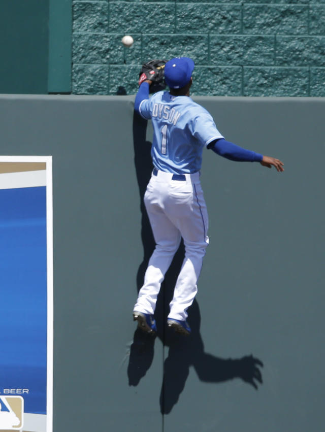Kansas City Royals center fielder Jarrod Dyson climbs the wall while chasing a home run hit by Detroit Tigers' Alex Avila during the fifth inning of a baseball game in Kansas City, Mo., Sunday, May 4, 2014. (AP Photo/Orlin Wagner)