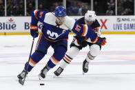 New York Islanders center Anders Lee (27) skates past Edmonton Oilers center Markus Granlund (60) during the second period of an NHL hockey game Tuesday, Oct. 8, 2019, in Uniondale, N.Y. (AP Photo/Kathy Willens)