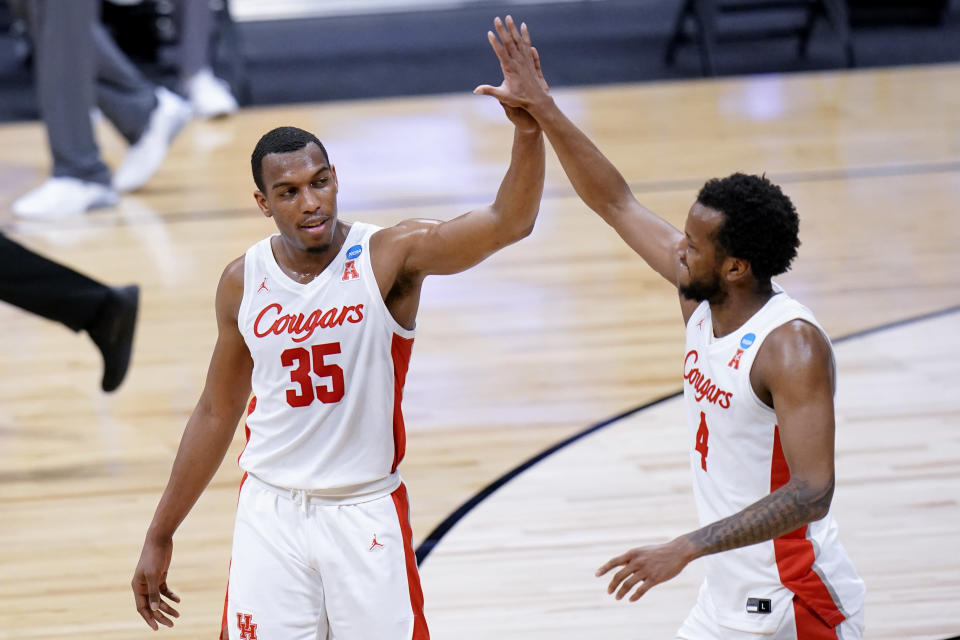 Houston forward Fabian White Jr. (35) and Justin Gorham (4) celebrate beating Syracuse 62-46 after a Sweet 16 game in the NCAA men's college basketball tournament at Hinkle Fieldhouse in Indianapolis, Saturday, March 27, 2021. (AP Photo/AJ Mast)