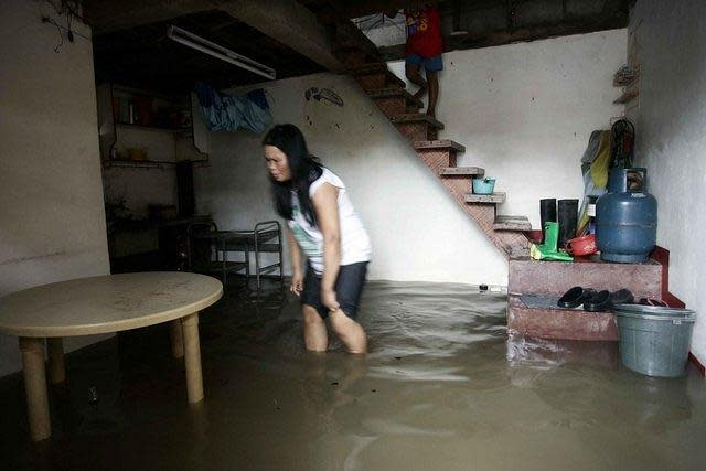 "A woman tries to do her chores inside a flooded home at Barangay Malanday in low-lying Marikina City, northeast of Manila, as rising floodwaters from continuous rains brought on by Typhoon 'Gener' have prompted Marikina City officials to prepare to forcibly evacuate residents from some high-risk areas after the water level at the Marikina River rose to 16 meters early today, raising the alert level at the river to ""2."" (Mike Alquinto/NPPA Images)"