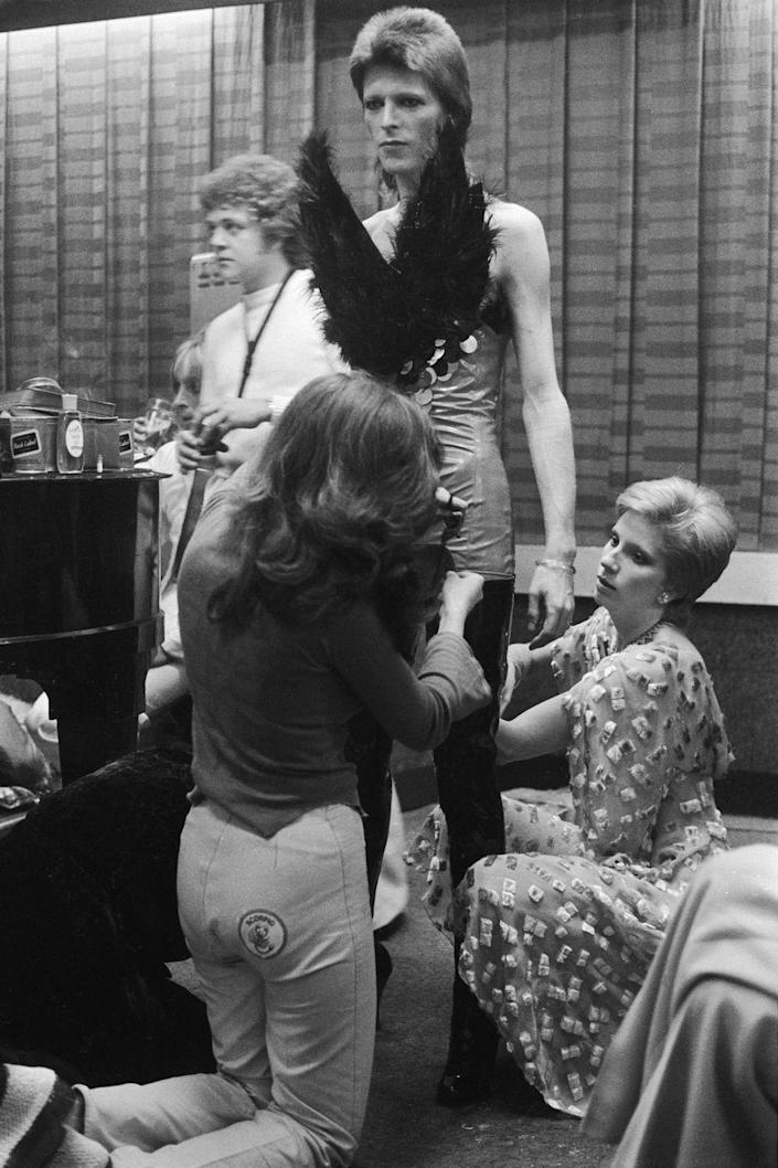 <p>David Bowie, preparing for a performance backstage, circa 1973. He is being dressed in an extravagant costume by his wife Angie Bowie (right) and an assistant.</p>