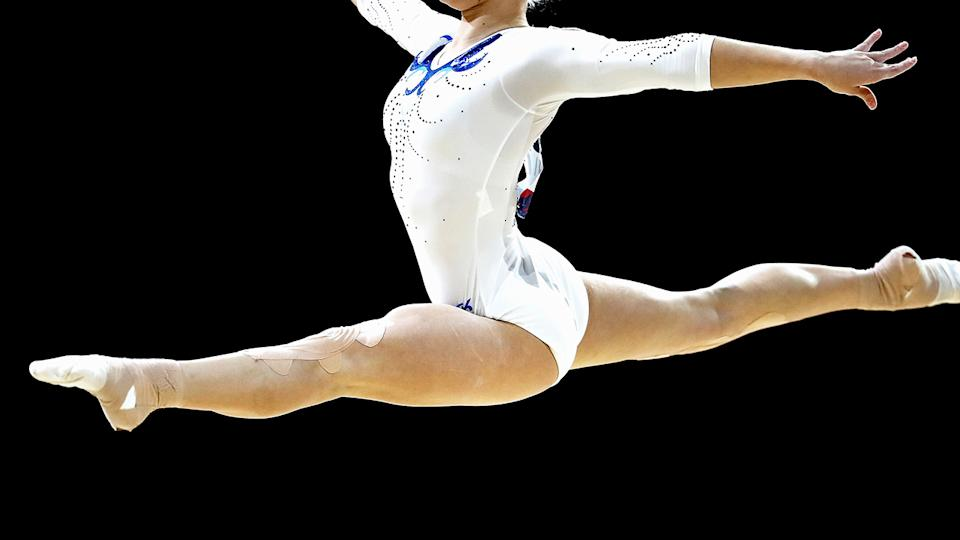 A female gymnast, pictured here in action on the beam.