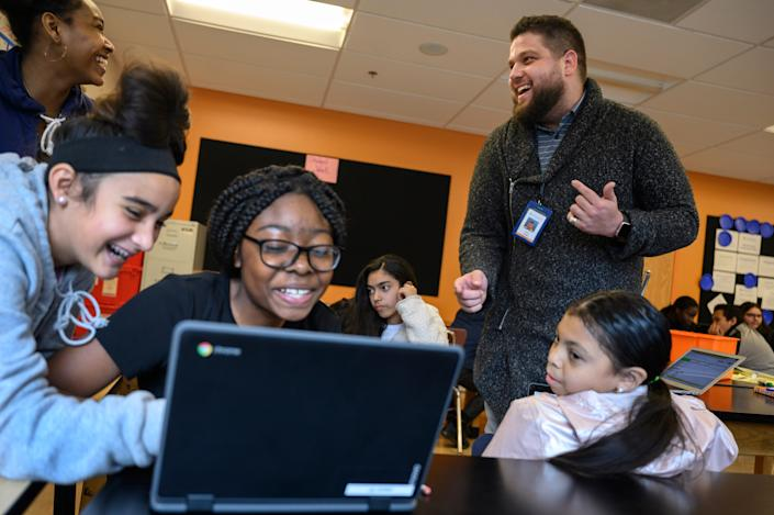 Justin Lopez-Cardoze, right, teaches a 7th grade science class at Capital City Public Charter School in Washington, DC on November 7, 2019. Lopez-Cardoze was named the city's teacher of the year last month and is using the $8,000 in prize money to set up a scholarship for a high school senior.