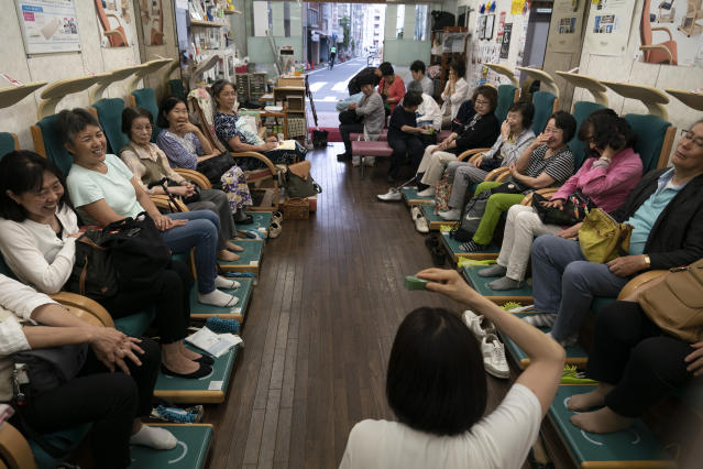 Sitting on treatment devices, a group of Japanese senior citizens laugh while listening to a demonstration on the devices in Tokyo, June 21, 2019. (AP Photo/Jae C. Hong)