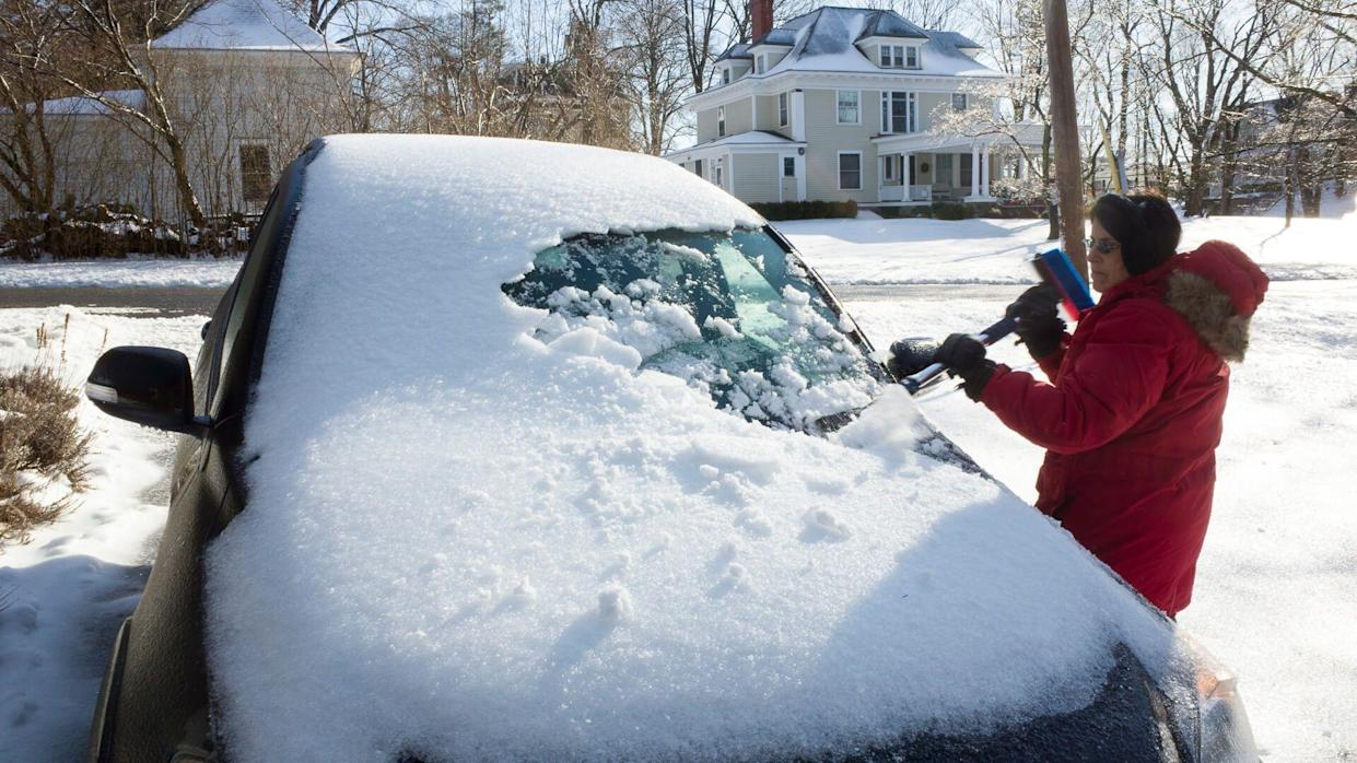 woman scraping snow off her car