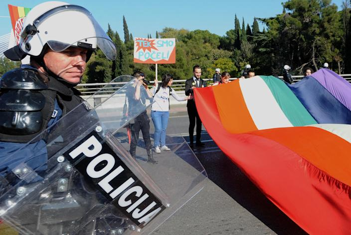 A police officer guards Montenegrin gay activists during a Gay Pride parade in the capital city Podgorica on November 2, 2014 (AFP Photo/Savo Prelevic)