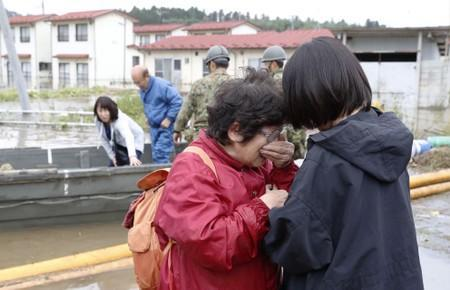 A woman cries in relief after being rescued from an area flooded by Typhoon Hagibis in Marumori, Miyagi prefecture