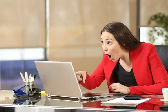 Young businesswoman in a red jacket points at her laptop screen with an expression of wide-eyed amazement on her face.
