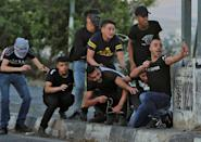 Palestinian protesters use slingshots during clashes with Israeli security forces at the Hawara checkpoint south of Nablus city, in the occupied West Bank, on May 17