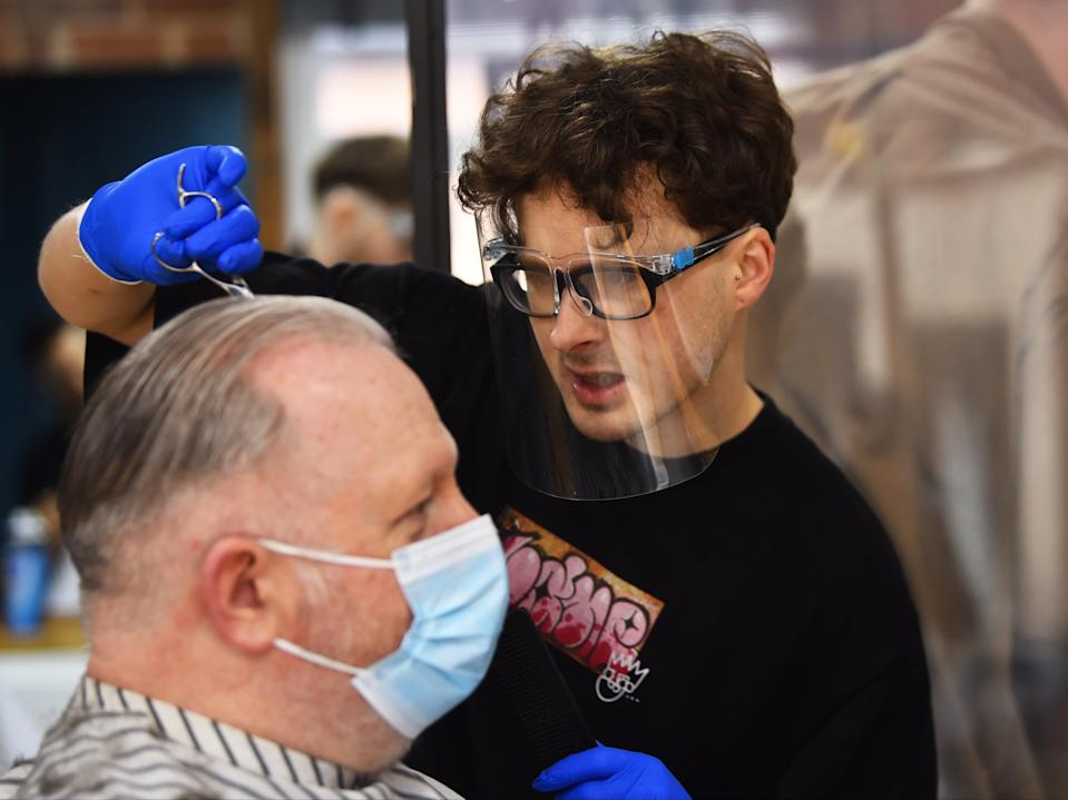 A man wearing a mask has his hair cut at The Men's Den Barber Shop in Leek, England (Getty Images)