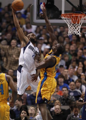 Dallas Mavericks forward Vince Carter, left, goes for a dunk against New Orleans Hornets center Emeka Okafor, right, during the first half of an NBA basketball game in Dallas on Saturday, Jan. 7, 2012. (AP Photo/Mike Fuentes)