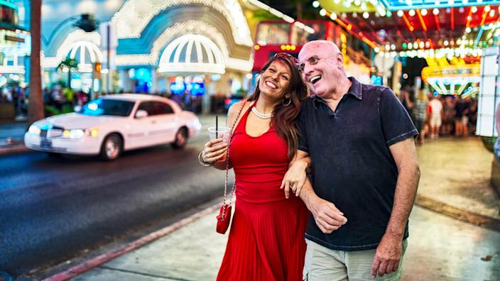 mature couple sightseeing in downtown las vegas streets at night.