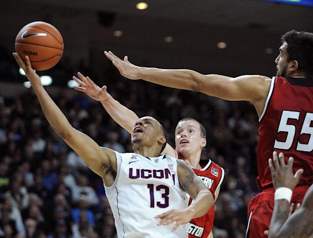 Connecticut's Shabazz Napier (13) drives past Eastern Washington's Parker Kelly (10) and Venky Jois (55) during the second half of an NCAA college basketball game in Bridgeport, Conn., Saturday, Dec. 28, 2013. Napier scored a team-high 15 points in his team's 82-65 victory. (AP Photo/Fred Beckham)