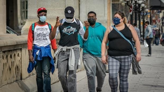 Wearing masks to protect against COVID-19, this group crosses the Rideau Canal in downtown Ottawa on Tuesday. Two days later, Ottawa Public Health reported 151 more COVID-19 cases, but another 79 cases are considered resolved.  (Brian Morris/CBC - image credit)