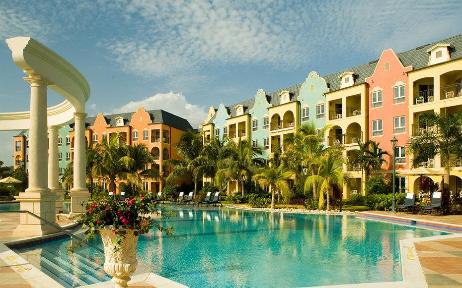"""With eight restaurants, six bars, and three pools (including the island's largest), Jamaica's <a rel=""""nofollow"""" href=""""http://www.travelandleisure.com/travel-guide/whitehouse/hotels/sandals-whitehouse-european-village-spa"""">only all-beachfront resort</a> has plenty to keep visitors busy—and that's without considering the entertainment. Each night there's a different tk, including everything from fire dancing and a piano bar to Carnival night. The all-inclusive property has four levels of guestrooms, some of which come with butler service. It's all set in a 500-acre nature reserve complete with a two-mile stretch of beach on the island's less-developed southern coast."""