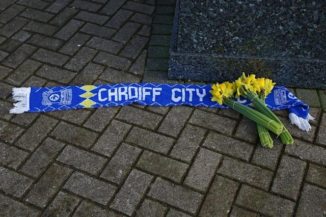 Bunches of daffodils and a Cardiff City scarf are left outside the club's stadium after news of the disappearance of the plane carrying their new signing Sala (AFP Photo/GEOFF CADDICK)