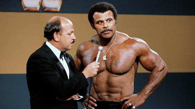 "In this undated photo provided by WWE, Inc., ""Mean"" Gene Okerlund interviews Rocky ""Soul Man"" Johnson. Johnson, a WWE Hall of Fame wrestler who became better known as the father of actor Dwayne ""The Rock"" Johnson, died Wednesday, Jan. 15, 2020. He was 75. (WWE, Inc. via AP)"