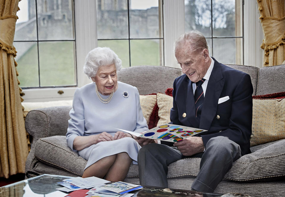 In this image released on Thursday Nov. 19, 2020, Britain's Queen Elizabeth II and Prince Philip, Duke of Edinburgh look at a homemade wedding anniversary card, given to them by their great grandchildren Prince George, Princess Charlotte and Prince Louis, as the royal couple sit in the Oak Room at Windsor Castle, England, Nov. 17, 2020, ahead of their 73rd wedding anniversary. Elizabeth married Philip on Nov. 20, 1947, at Westminster Abbey in London. Prince George, Princess Charlotte and Prince Louis are the children of Prince William and Catherine, Duchess of Cambridge, and great-grandchildren to Queen Elizabeth and Prince Philip. (Chris Jackson/Pool via AP)