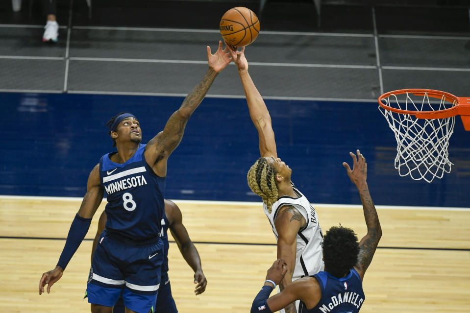 Minnesota Timberwolves forward Jarred Vanderbilt (8) and Brooklyn Nets forward Nicolas Claxton reach for a rebound during the first half of an NBA basketball game Tuesday, April 13, 2021, in Minneapolis. (AP Photo/Craig Lassig)
