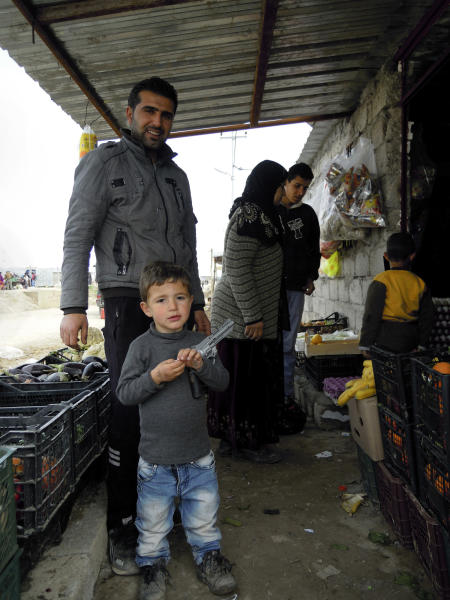 In this Friday, Feb. 15, 2013 photo, Syrian Kurdish refugees Khader Qassem, 30, poses with his son, Abdel Qader, 4. outside his grocery store in the Dumiz refugee camp in northern Iraq. Syrian Kurds who fled their country's civil war have mixed feelings about a future without Bashar Assad: They hope to win autonomy if the regime falls, but fear chaos and the rise of Islamists could instead make their lives worse. (AP Photo/Karin Laub)