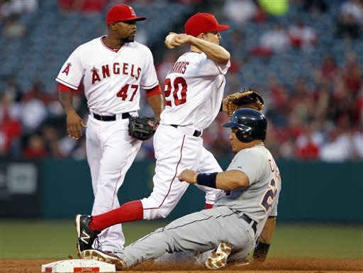 Los Angeles Angels shortstop Brendan Harris (20) forces out Detroit Tigers' Miguel Cabrera, right, to end the first inning, with Los Angeles Angels second baseman Howie Kendrick (47) looking on, during a baseball game Friday, April 19, 2013, in Anaheim. (AP Photo/Alex Gallardo)