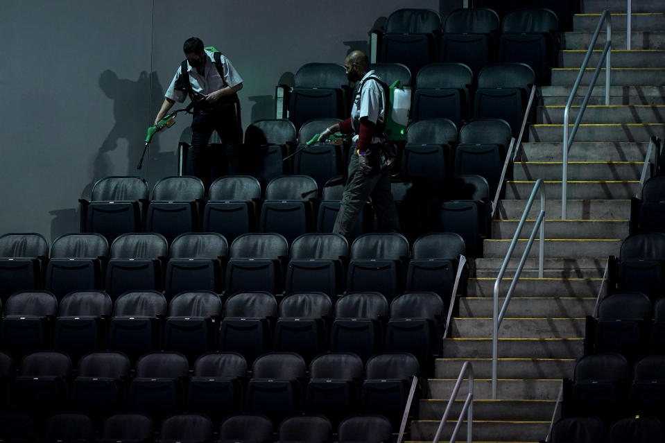 Workers sprays disinfectant on seats to prevent the spread of COVID-19 at the T-Mobile Center between sessions at the Big 12 Conference NCAA college basketball tournament in Kansas City, Mo., Thursday, March 11, 2021. (AP Photo/Charlie Riedel)