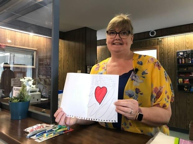 Annette Mason holds up the card that the Hope sisters made for the staff of the Snowshoe Inn.