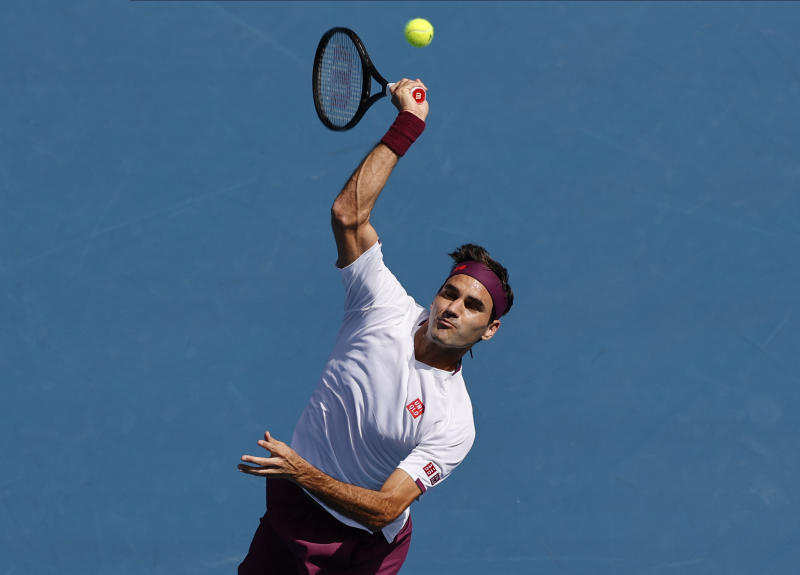 Switzerland's Roger Federer makes a forehand return to Tennys Sandgren of the U.S. during their quarterfinal match at the Australian Open tennis championship in Melbourne, Australia, Tuesday, Jan. 28, 2020. (AP Photo/Andy Wong)