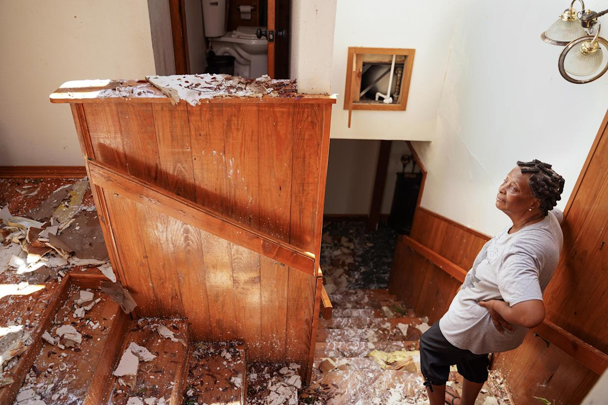 Patricia Henderson stands in the stairway at her home, which lost its roof during Hurricane Ida, on Tuesday in Ponchatoula, La.