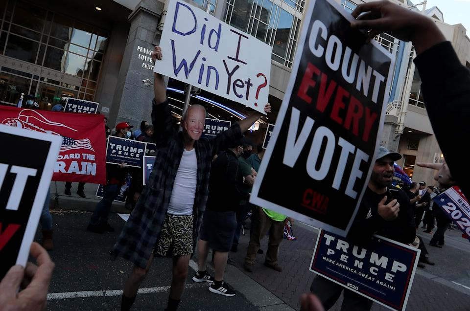 """A supporter of President Trump wears a mask of challenger Joe Biden's face while holding a """"Did I win yet?"""" sign"""