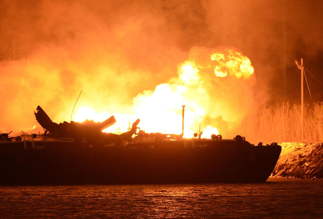 A massive explosion at 3a.m. EDT on one of the two barges still ablaze in the Mobile River in Mobile, Ala., on Thursday, April 25, 2013. Three people were injured in the blast. Fire officials have pulled units back from fighting the fire due to the explosions and no immediate threat to lives. (AP Photo John David Mercer) Three people were hospitalized with burns. Information on their conditions was not immediately available.