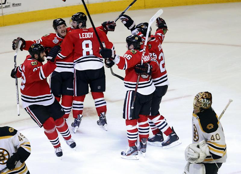 Chicago Blackhawks center Andrew Shaw, second from left, celebrates with his teammates after scoring the winning goal during the third overtime period of Game 1 in their NHL Stanley Cup Final hockey series against the Boston Bruins, Thursday, June 13, 2013, in Chicago. The Blackhawks won 4-3. (AP Photo/Charles Rex Arbogast)