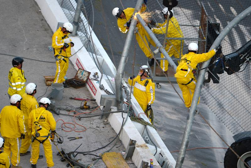 Track workers repair the safety fence along on the front grandstands, where Kyle Larson's car hit it on the final lap of the NASCAR Nationwide Series auto race at Daytona International Speedway in Daytona Beach, Fla., Saturday, Feb. 23, 2013. (AP Photo/Phelan M. Ebenhack)