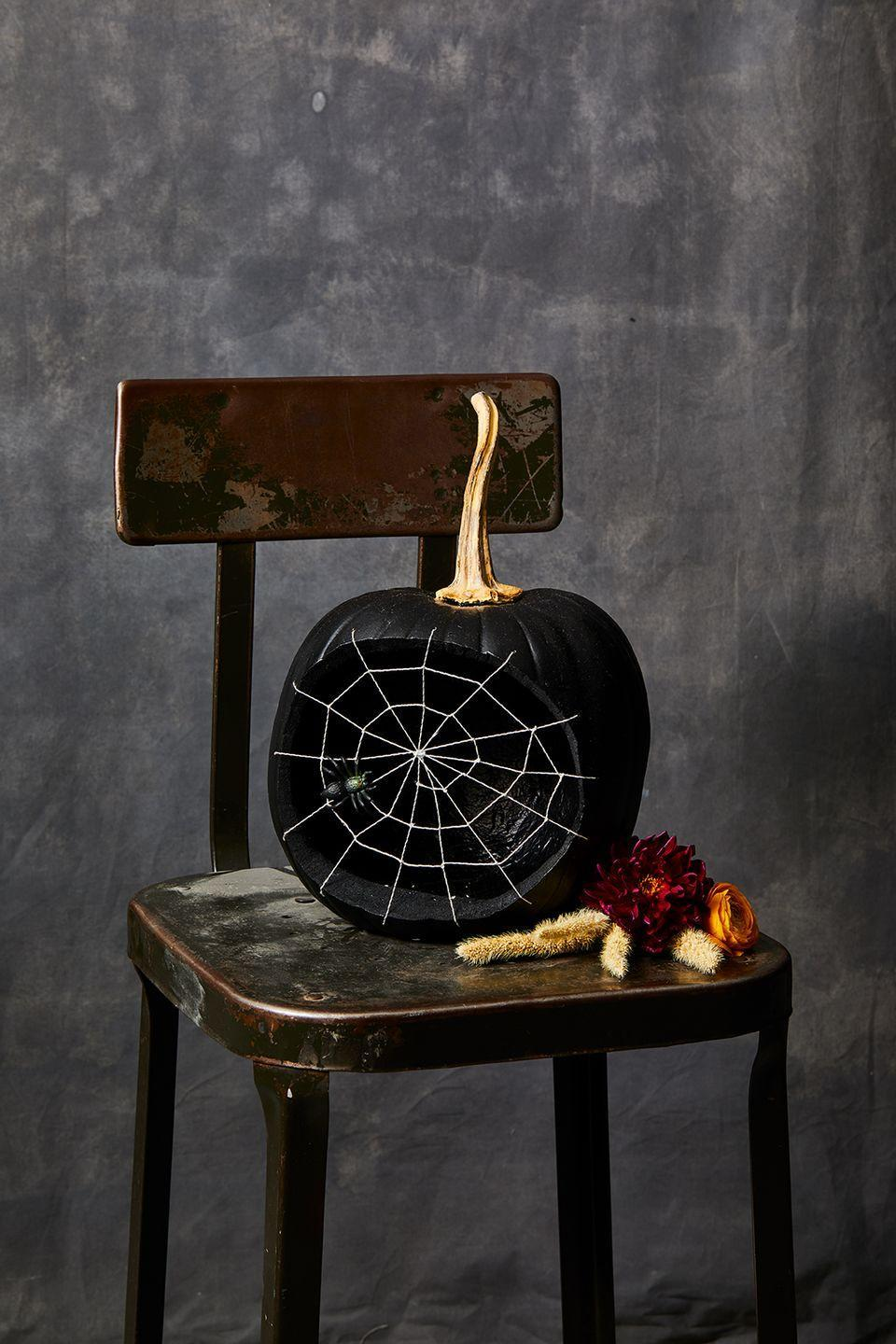 <p>This spooky spider pumpkin will look great on your front porch or anywhere in your house! Simply carve out a circle on the face of the pumpkin, spray paint it (inside and outside) black, and poke 12-13 holes along the edge where you carved. Then, thread a needle with a metallic string and tie a knot on the end. Start from the inside and pull the thread through the first hole, then through another hole directly across the pumpkin (poking the pumpkin from the outside) and tying it off inside. Repeat this step until you have all your holes filled. Take a length of string and start by tying it to one of the crisscrossed strings you just created about 1 inch from the outside of the hole. Continue making a spiral by knotting as you hit the crisscross that is already there, continuing in a circular swirl. For the final touch, add a spider to your web!</p>