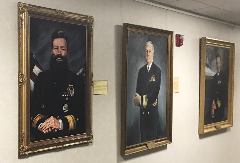 CORRECTION: TAKES OUT REFERENCE OF OFFICIAL ARTIST'S PORTRAIT ADDS INFORMATION ABOUT PORTRAIT:  This May 2019 photo provided by U.S. Naval War College president Rear Adm. Jeffrey Harley, shows a portrait of Harley, left, displayed in a gallery in Conolly Hall on the school's campus in Newport, R.I. Harley, who is bald, said the portrait was made by a professor who paid for it himself and gave it to Harley as a joke. He called it a way to poke fun of himself.  Dozens of emails, which span from December 2017 to May 2019, were shared with The Associated Press by people at the war college who said they were concerned about Harley's leadership and judgment.  (Rear Adm. Jeffrey Harley/U.S. Naval War College via AP)