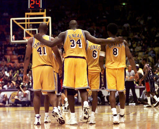 Los Angeles Lakers center Shaquille O'Neal (34) puts his arms around teammates, Elden Campbell (41) and Kobe Bryant (8) as Eddie Jones (6) and Derek Harper walk in front as they return to play the Houston Rockets in the fourth quarter at the Great Western Forum in Inglewood, Calif., Feb. 5, 1999. (AP Photo/Victoria Arocho)