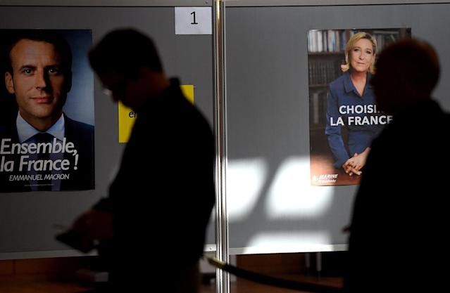 <p>French nationals stand in a line next to posters depicting presidential candidates Emmanuel Macron and Marine Le Pen as they wait to cast their votes at a polling station in the French Embassy in Moscow, May 7, 2017. (Vasily Maximov/AFP/Getty Images) </p>
