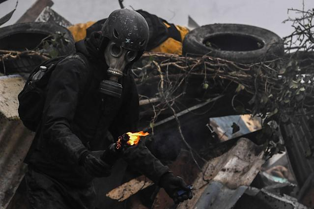 <p>A protester is about to throw a Molotov cocktail at riot forces as clashes erupt on April 10, 2018 during a police operation to raze the decade-old camp known as ZAD (Zone a Defendre – Zone to defend) at Notre-Dame-des-Landes, near the western city of Nantes, and evict the last of the protesters who had refused to leave despite the government agreeing to ditch a proposed airport. (Photo: Loic Venance/AFP/Getty Images) </p>