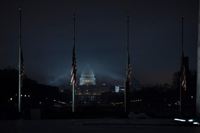 The U.S. flag flies at half-staff in front of the Washington Monument and U.S. Capitol in tribute to former President George H.W. Bush, early on Dec. 2. (Photo: Alex Edelman/AFP/Getty Images)