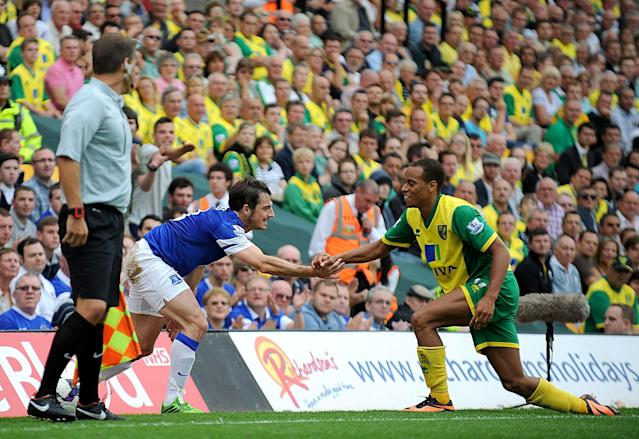Everton's Leighton Baines (left) and Norwich City's Elliott Bennett help each other up after a fall